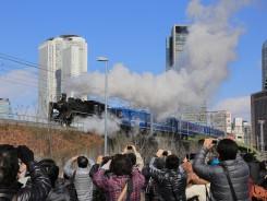 名古屋市中心部のビル街を通過するSLを見に集まった人たち(16日、名古屋市)